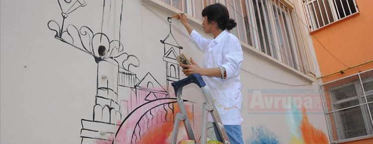 Resim öğretmenleri fırçalarıyla okul duvarlara  eğitici resimler yapıyor
